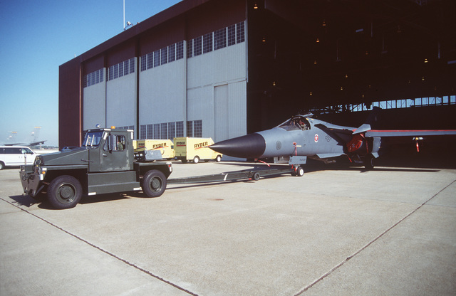 An F-111 from 523rd Fighter Squadron, Cannon Air Force Base, New Mexico is pulled out of a hangar after having maintenance performed
