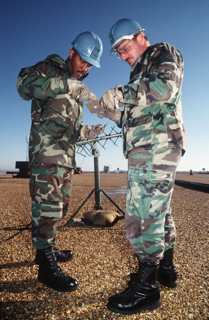 SENIOR AIRMAN Carl Peguese (left) and Technical Sergeant James McLean, members of the 27th Fighter Wing, Wing Initial Communication Package, Cannon Air Force Base, set up a radar system on top of a hangar. This is part of a four day exercise involving Navy, Army, Air Force, Marines and Coast Guard to test proficiency in joint operations and coordination of various elements of a strike package