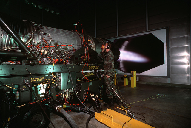 """USAF SENIOR AIRMAN Eric D. Middaugh assigned to the 35th Fighter Wing, Misawa AB, Japan searches for furl leaks, while an F-16 aircraft engine runs at full afterburner inside one of Misawa's new aircraft engine test facilities called """"Hush Houses"""". From AIRMAN Magazine's February 1995 issue article """"Source of the Sun"""""""