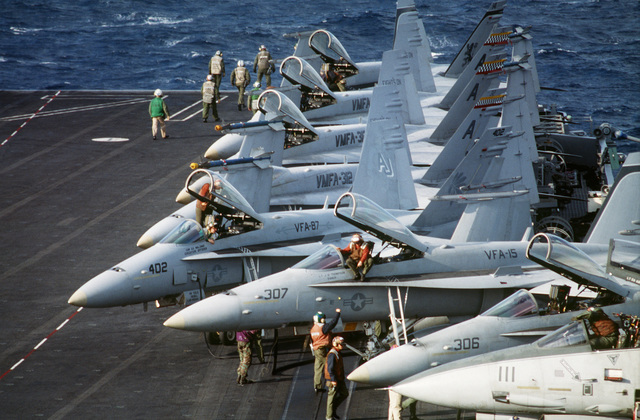 A line of F/A-18 Hornets sit on the flight deck of the USS THEODORE ROOSEVELT (CVN-71). This is part of a four day exercise involving Navy, Army, Air Force, Marines and Coast Guard to test proficiency in joint operations and coordination of various elements of a strike package