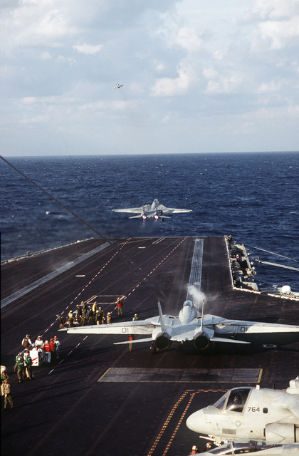 A Navy F-14A Tomcat catapults off the deck of the USS THEODORE ROOSEVELT (CVN-71) as another is positioned for take-off. This is part of a four day exercise involving Navy, Army, Air Force, Marines and Coast Guard to test proficiency in joint operations and coordination of various elements of a strike package