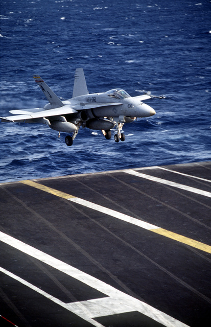 An F/A-18 Hornet, assigned to USS THEODORE ROOSEVELT (CVN-71) is just before touchdown on the carrier flight deck. This is part of a four day exercise involving Navy, Army, Air Force, Marines and Coast Guard to test proficiency in joint operations and coordination of various elements of a strike package