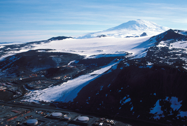 A view of a portion of McMurdo Station as seen from Observation Hill (elevation 750 feet). A snow covered mountain peak is in the background