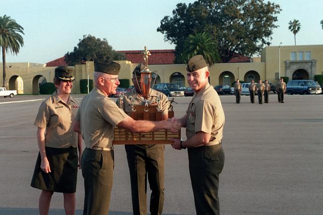 Brig. GEN. E. C. Kelly, Jr., Depot Commanding General (left) presents the CG's Cup to Colonel J. P. Wright, Commanding Officer, Headquarters and Service Battalion. The battalion SGT. MAJ., Stanley Hillery helps to hold the cup