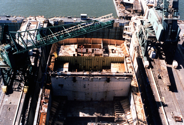 An overhead view looking down from the 350 ton crane, at the traverse bulkhead arrangement of the stern section of the Military Sealift Command's new vehicle transport ship USNS GILLILAND (T-AKR 298) under conversion in drydock #11 at Newport News Shipbuilding and Drydock Corporation on the James River
