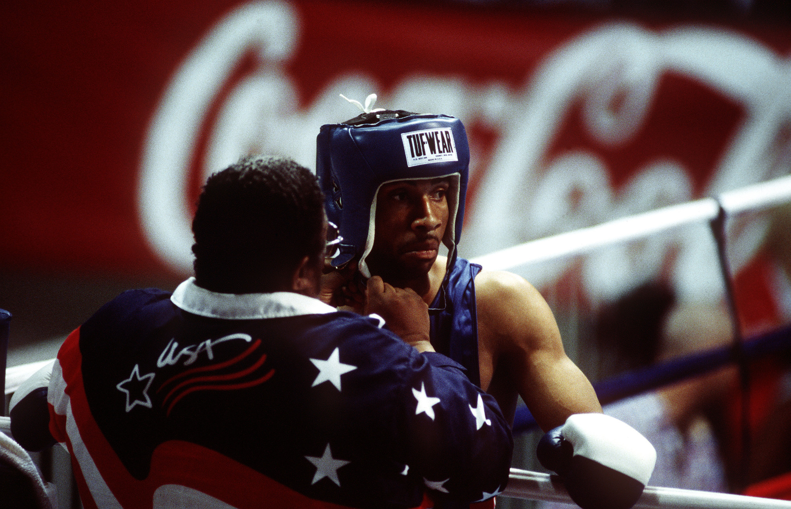 Boxing Coach Tom Mustin fastens the head protector on Air Force Boxer, STAFF SGT. Ron Simms, prior to his second middleweight match against Marcus Thomas of Barbados at the Pan Am boxing venue Club Athletico Once Unidos