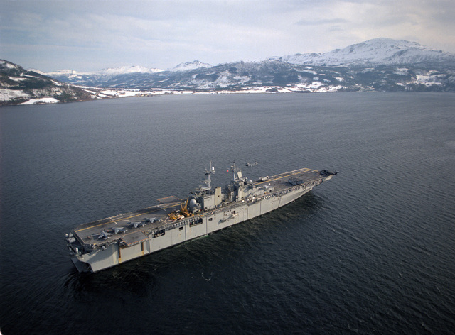 Aerial starboard quarter view of the amphibious assault ship USS WASP(LHD-1) transiting the Surnadal Fjord at the conclusion of exercise Strong Resolve '95