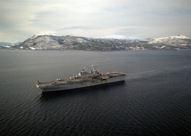 An aerial port bow view of the amphibious assault ship USS WASP (LHD-1) departing the Surnadal Fjord at the conclusion of Exercise Strong Resolve '95