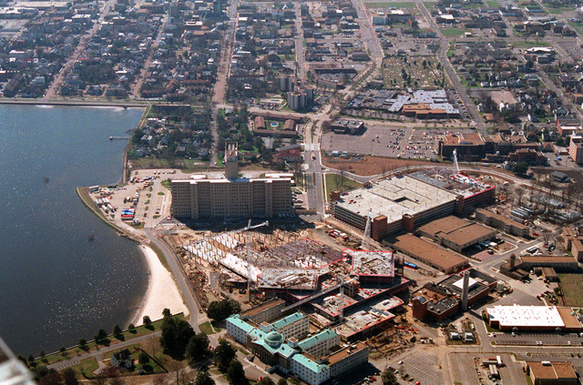 An aerial view of the Portsmouth Naval Hospital complex. At the bottom right is the old original hospital now used for pediatrics. Above that is construction for the new extension and above that is the new hospital. The large building to the right is the new parking garage