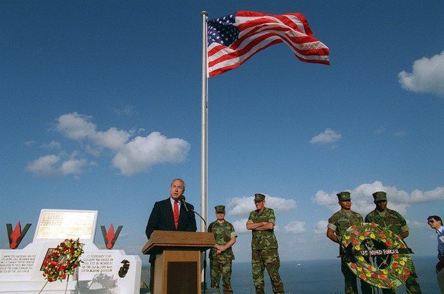 """Secretary of the Navy John H. Dalton addresses a large group of active duty military and veterans attending the 50th anniversary memorial ceremony atop Mount Suribachi. He stated """"Honor, courage, commitment as words, they are easy to say. Here on Iwo Jima, they were turned into deeds, deeds that will forever guide the Naval service"""". Also present for the ceremony were General Carl E. Mundy, Jr. Commandant of the Marine Corps (rear left) and Admiral Richard C. Macke, Commander-In-CHIEF, U.S. Pacific Command (rear left)"""