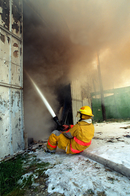 Fire fighter Aviation Boatswain't Mate (Aircraft Handler) Second Class (ABH2) Tracey Mackey helps extinguish a fire in the housing office warehouse, Bldg. 590, which holds loaner furniture