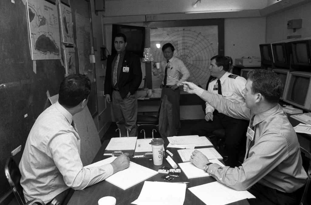 The Naval Component Commander players discuss operations in one of the second deck command cells in Sims Hall, Naval War College. From left are LT. CMDR. Aziz Alchouche of Morocco, LT. CMDR. Ronen Nimi of Israel, LT. CMDR. Hsing-Biau Jiang of the Republic of China and LT. CMDR. Jack Federoff, lower right of the United States. (The commander at upper right is unidentified.)