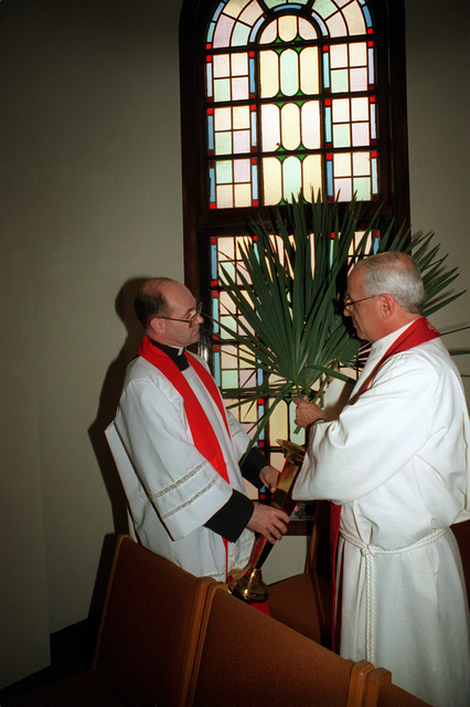 Chaplain (LT. CMDR.) Anthony Trapani (right) is assisted by another chaplain in the arrangement of palm fronds at the Chapel of Hope in preparation for Palm Sunday and the beginning of Holy Week. LT. CMDR. Trapani is the Navy Educational Training Center (NETC) staff chaplain