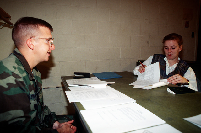 """STAFF SGT. Yocum (left), NCOIC of the Joint Information Bureau Command Information Section, reviews the ground rules for the civilian press with """"role player"""" AIRMAN 1ST Class Suzanne Rogers, 1ST Combat Camera Squadron, Charleston Air Force Base, S.C., during preparations for the exercise"""