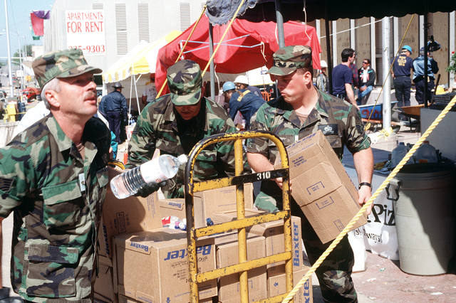 TECH. SGT. Ken Walker (left), TECH. SGT. J. D. Sagor (center) and STAFF SGT. Michael Hagood from Tinker Air Force Base, Oklahoma, work to pass out bottles of water to rescue and support personnel at the explosion site of the Federal Building. The U.S. Air Force is providing around-the-clock support of personnel, equipment and supplies during rescue and relief efforts
