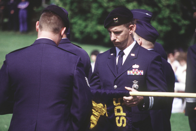 Captain Stephen L. Hutchens, 774th Security Police Commander, prepares squadron flag to be incased during the 774th ABG inactivation ceremony