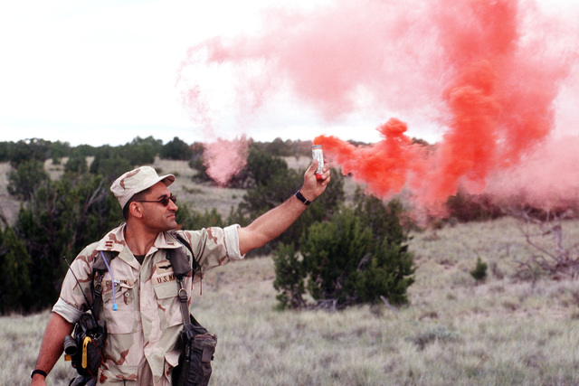 LT. Guertin, survivor from a simulated F-18 crash, uses a red died smoke to show where they are so the rescue team can find them somewhere in the New Mexico Desert