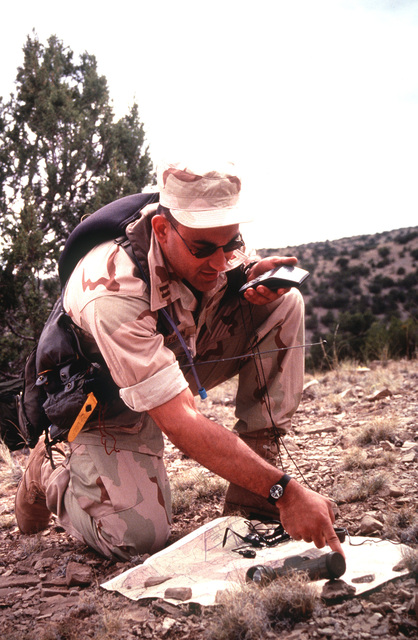 US Navy LT. Guertin, role playing as a survivor from a simulated F-18 crash, uses a portable global positioning system to pinpoint his location on a map of the state of New Mexico during the annual air defense exercise
