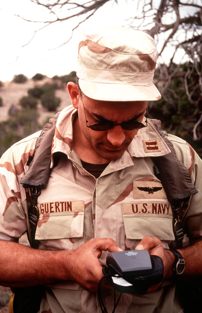 US Navy LT. Guertin, role playing as a survivor from a simulated F-18 crash, uses a portable global positioning system during the annual air defense exercise