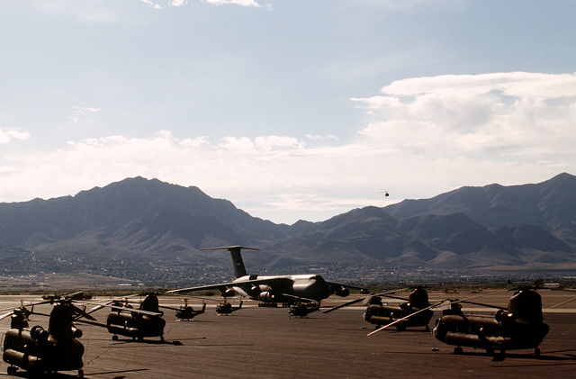An AMC C-5B Galaxy from the 60th AMW at Travis AFB, CA arrives at Biggs Army Air Field in El Paso, TX. The C-5 is bringing in 6 UH-1H helicopters and 1 OH-58 helicopter from the 2d-228 Aviation Regiment U.S. Army Reserve from Willowgrove, PA. In the foreground are four CH-47 Chinook helicopters and three UH-1 Iroquois