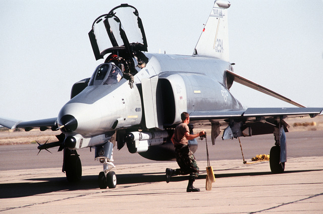 "CAPT. Wenke ""Wee Willy"" Scott and CAPT. George ""Jorge"" Thomas from the 124th Fighter Group, Boise IAP, Idaho, do their preflight checks inside an F-4 Phantom prior to take-off while a crew member runs to remove the chocks at the Roswell Industrial Air Center"