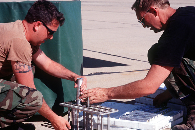 MASTER SGT. Bud Schiwart and STAFF SGT. Dale DeAngee, both from the 152nd Tactical Reconnaissance Group, Reno, Nevada, place tubes connected with the weapons system on the aircraft into Styrofoam cases at Roswell Industrial Air Center
