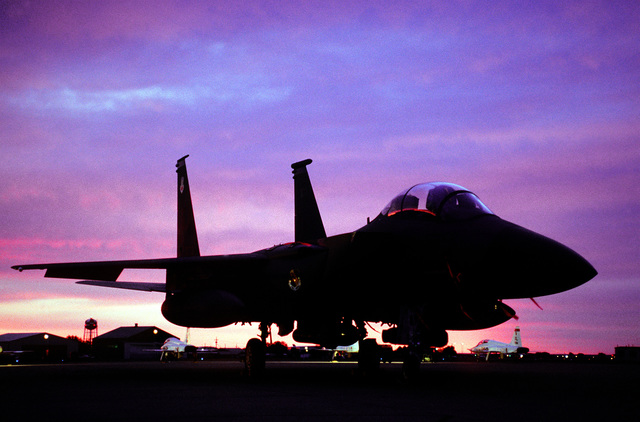 An F-15 Strike Eagle from the 334th Fighter Squadron Seymour Johnson, AFB, NC, sits on the ramp as the sunrise starts a new day at Roswell Industrial Air Center