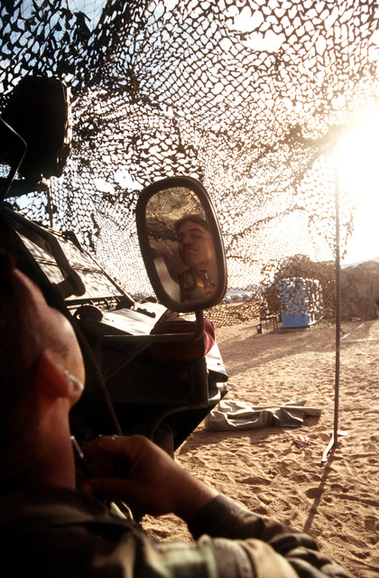U.S. Army PFC. Michael Cellis, sampler/communications operator, 2nd Squad, 1ST Platoon, 51st Chemical Company, Fort Polk, Louisiana, uses the side mirror of a Fox vehicle to shave. This company operates the unique Fox vehicle which is used to detect chemical and biological contaminants from the safety of a fully pressurized armored amphibious vehicle