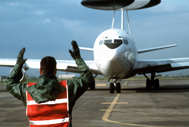A ground crewman directs a US Air Force E-3 Sentry Airborne Warning and Control System (AWACS) aircraft from its parking spot. The aircraft is beginning a mission over Turkey in support of the operation. This operation is a security mission to enforce the United Nations no-fly zone north of the 36 degree parallel from Iraqi air and ground incursion. A four nation coalition of US, Turkey, Great Britain and France has been actively protecting and supplying Kurdish refugees since Desert Storm in 1991.(Exact date unknown)