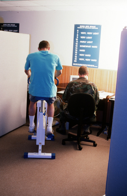 """A rear view of a USAF fitness monitor as he records the results of person taking the Air Force cycle ergometry test. From AIRMAN Magazine's May 1995 issue """"Cycle Ergometry: Shifting Gears"""""""