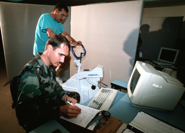 """A USAF fitness monitor records the results of person taking the Air Force cycle ergometry test. From AIRMAN Magazine's May 1995 issue """"Cycle Ergometry: Shifting Gears"""""""