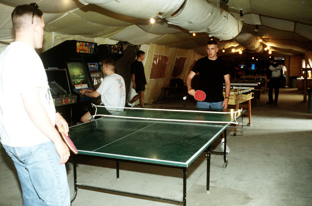 AIRMAN 1ST Class Thomas Crum (left) and AIRMAN 1ST Class Paul Wilbur play ping pong in the morale tent. This operation is a security mission to enforce the United Nations no-fly zone north of the 36 degree parallel from Iraqi air and ground incursion. A four nation coalition of US, Turkey, Great Britain and France has been actively protecting and supplying Kurdish refugees since Desert Storm in 1991.(Exact date unknown)