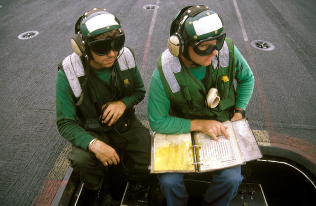 Aviation Boswains Mate (engineer) Third Class (ABM3) Robert W. Wickelhaus and Aviation Boswains Mate Second Class (ABM2) Butch Grawodos provide flight crew and catapult system operators with valuable data on aircraft type, weight, ordnance, wind speed and direction before each aircraft launch on board the aircraft carrier USS INDEPENDENCE (CV-62)