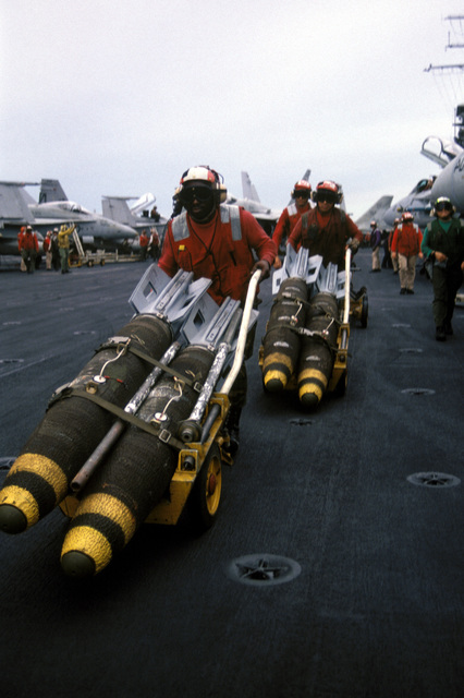 Aviation Ordnanceman Second Class (AO2) Darrell Thomas leads a crew transporting Mark 82 500 pound drag bombs to the forward flight deck of the aircraft carrier USS INDEPENDENCE (CV-62) for eventual load-out of aircraft