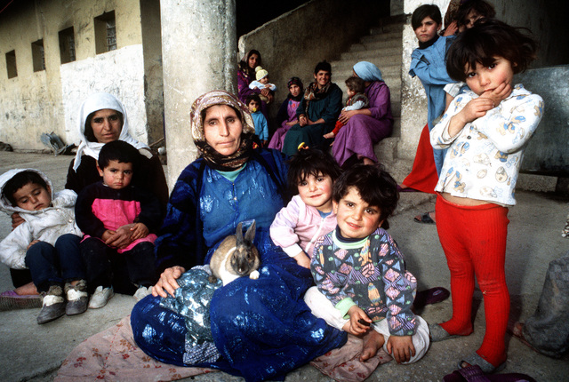 Kurdish women and children pose for photograph outside Nazarki Prison in Northern Iraq. This operation is a security mission to enforce the United Nations no-fly zone north of the 36 degree parallel from Iraqi air and ground incursion. A four nation coalition of US, Turkey, Great Britain and France has been actively protecting and supplying Kurdish refugees since Desert Storm in 1991.(Exact date unknown)