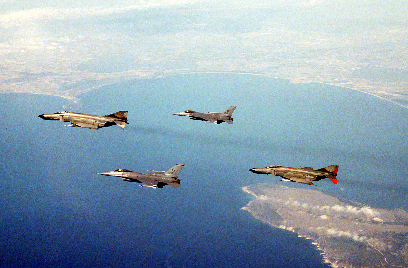 Two US Air Force F-16 Fighting Falcons, from the 510th Fighter Squadron, Aviano, Italy, fly with German F-4's, for a training exercise. Exact Date Shot Unknown