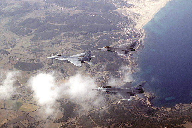 Two U.S. Air Force F-16 Fighting Falcons from the 510th Fighter Squadron, Aviano AB, Italy, fly with a German MiG-29A on a training exercise