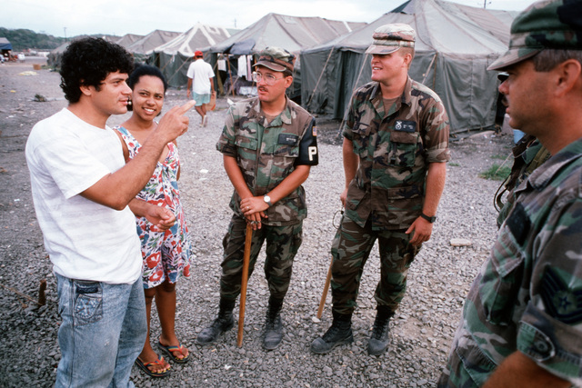 """USAF AIRMAN First Class (A1C) Dean S. Johnson, Lackland AFB, Texas, A1C Todd A. Edwards and Technical Sergeant Mark McGee, Davis-Monthan, Arizona talk to a Cuban couple inside Safe Haven Camp 2, located at Guantanamo Bay, Cuba, the airmen are assigned to security detail inside the Camp. From AIRMAN Magazine's May 1995 issue article """"Trail of Dreams"""""""