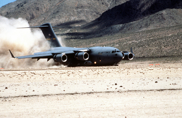 A U.S. Air Force C-17 Globemaster III uses reverse thrusters to slow down during a landing on a desert runway at the National Training Center. The exercise was designed to test the ability of the C-17 to support mission requirements and interface with the Army
