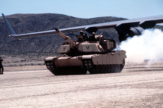 A U.S. Army M-1 Abrams Main Battle Tank rolls away from a U.S. Air Force C-17 Globemaster III on a desert airstrip at the National Training Center. The exercise was designed to test the ability of the C-17 to support mission requirements and interface with the Army. The C-17 delivered the tank to the desert airstrip as part of the review