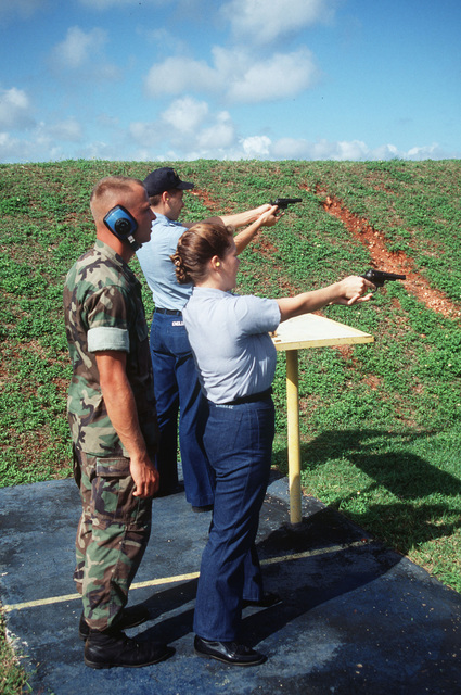 Photographers Mate AIRMAN (PHAN) Arron England and Photographers Mate Third Class (PH3) Heather S. Gordon are shown during .38 caliber revolver qualifications at NCTAMS pistol range on Guam. They are being instructed by SGT. Scott Wesierski, one of the range safety officers
