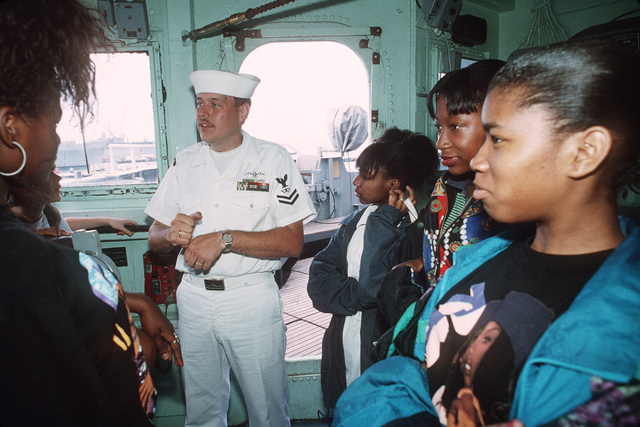 Fire Control Technician Second Class (FC2) Michael L. Glass explains the bridge operations of the guided missile cruiser USS BAINBRIDGE (CGN-25) to students of a local school during a tour of the ship as part of the ships community service program