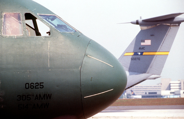 A close right front view of the nose section and a medium left view of the tail section of two C-141 Starlifters on the flightline for deployment. The Starlifters will be used to airlift US Army soldiers and cargo to the training area near L'viv, Ukraine, for humanitarian and peacekeeping exercises