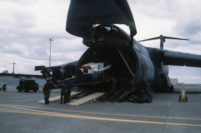 Crews roll a newly delivered UH-1N helicopter out of a C-5 transporter onto the flight line. The helicopter which was originally used by the 58th Airlift Squadron at Ramstein Air Base, Germany, was sent to the 40th Rescue Flight