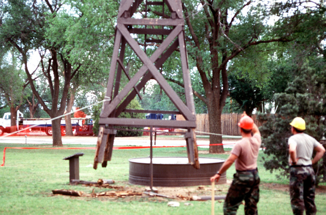 The foundation of the windmill being removed is cut loose and the swinging frame is stabilized by cable. During periods of draught it pumped water from under the parched west Texas ground to the arid surface