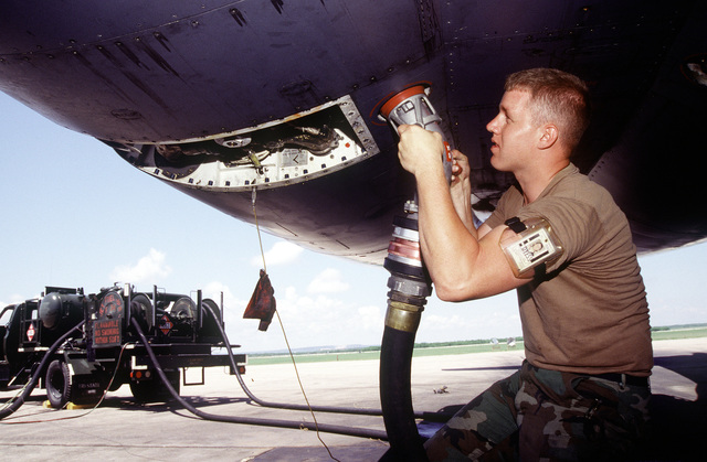 "SENIOR AIRMAN Brian Bower, crew chief, attaches a refueling nozzle to the fuel receptacle of a B-1B Lancer bomber. This aircraft is participating in exercise CORONET BAT a non-stop around the world sortie, that will include five in-flight refuelings, and three ""no-drop"" bombing exercises. When completed this will establish the first (unofficial) world record in this weight category"
