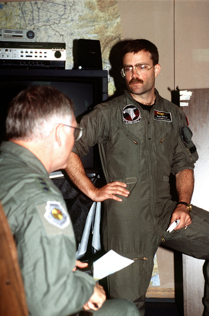 US Navy CAPT. Brian Hinkley, a pilot with the Navy EA-6 Shadowhawks, debriefs US Air Force LT. GEN. Mike Ryan at a mass hot wash following the rescue mission of CAPT. Scott O'Grady. CAPT. O'Grady's F-16 Fighting Falcon was shot down over Bosnia on June 2, 1995, while he was flying in support of Operation Deny Flight. After 6 days of evasion he was rescued by US Marines from the 24th Marine Expeditionary Unit, deployed from the USS KEARSAGE (LHD-3).(Exact date unknown)