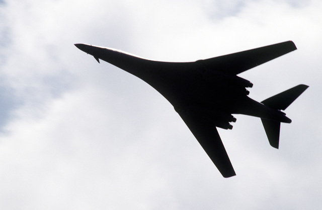 """Silhouetted against the clouds above, """"Hellion"""" the lead B-1B Lancer aircraft of the 9th Bomb Squadron, Dyess Air Force Base, Texas, makes a high speed fly over during exercise CORONET BAT. This was an around the world mission that included five in-flight refuelings, and three """"no-drop"""" bombing exercises. This will also determine the world record in this weight category"""