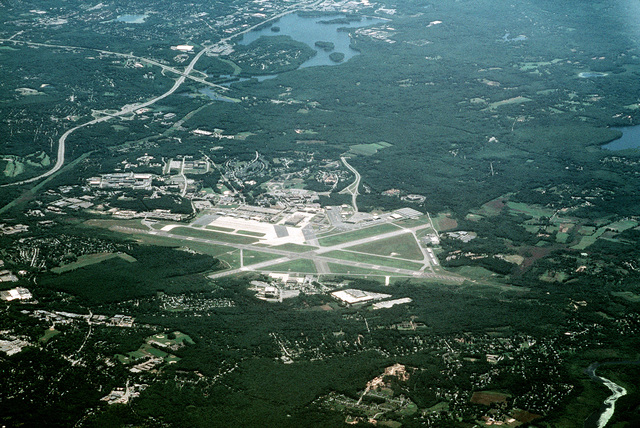 High oblique aerial view, looking south of Hanscom Air Force Base, Massachusetts.  This joint use civil and military airfield is the US Air Force Electronic Systems Center under the Air Force Material Command.  The facility is responsible to provide research, development, training and evaluation (RDT&E) of command, control communication, computer intelligence (CCCCI) interface with industry