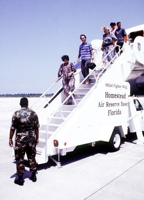 Cubans migrants are greeted by U.S. Air Force personnel at Homestead Air Force Base, Florida. As they head for a processing center for Immigration and Naturalization Service Interviews